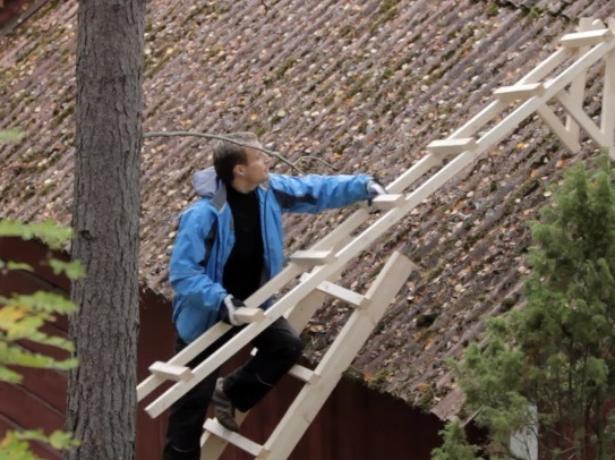 Рабочий устанавливает лестницу