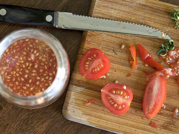 Разрезанные томаты и ёмкость с семенами