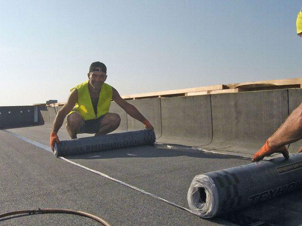 Рабочие монтируют гидроизоляционный материал