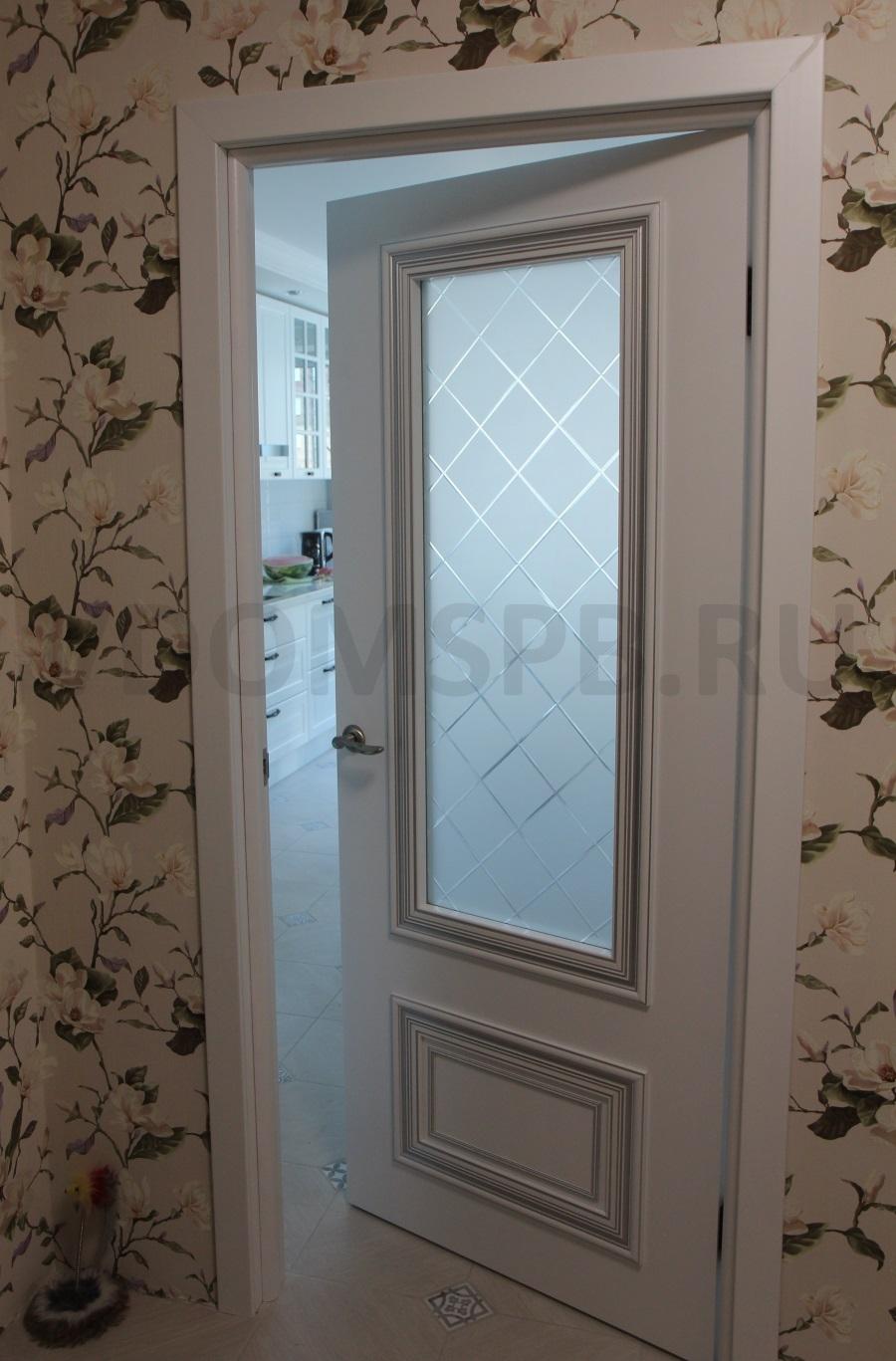 Белая дверь с широким фигурным багетом и патиной