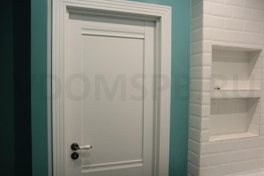 белая дверь и зеленые стены в ванной