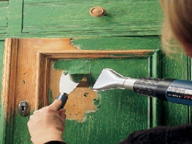 Рабочий снимает старый слой краски