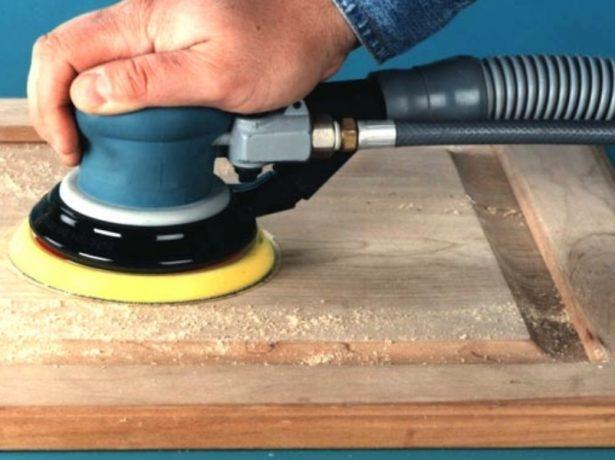 Рабочий шлифует деревянную поверхность
