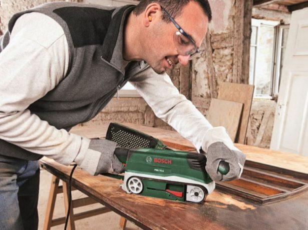 Рабочий шлифует деревянное полотно