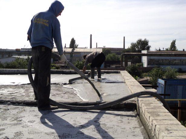 Рабочий покрывает крышу пенобетоном