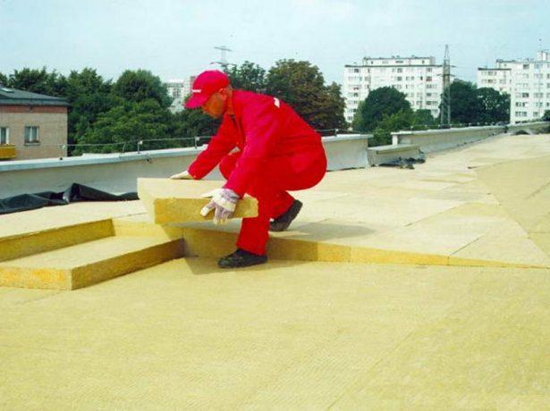 Рабочий укладывает утеплитель на крышу