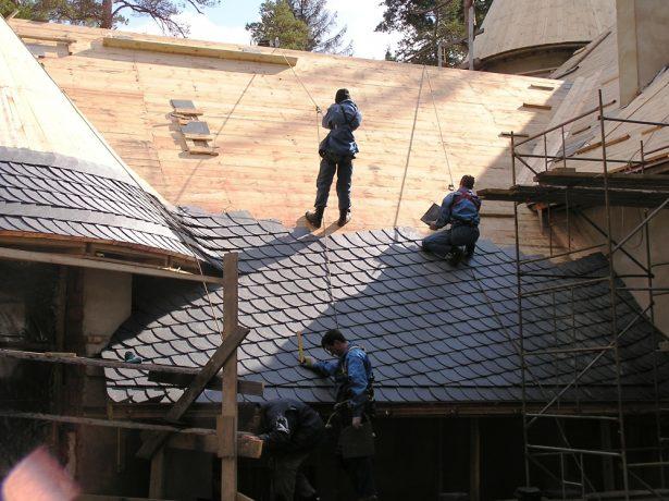 Рабочие монтируют сланцевые плитки