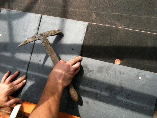 Рабочий укладывает плитки по разметке