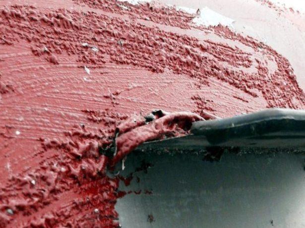 Рабочий удаляет краску шпателем