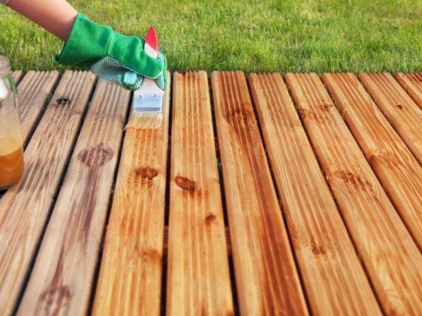Рабочий наносит морилку на деревянные доски